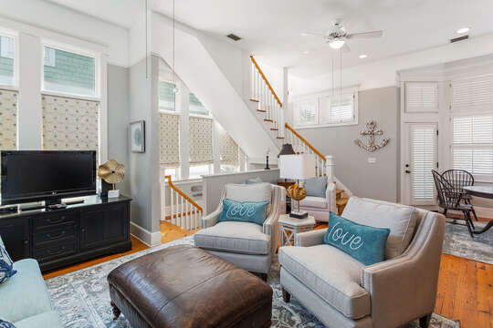 The living area of this beach house in St. Simons Island in the second floor, with TV and seating.