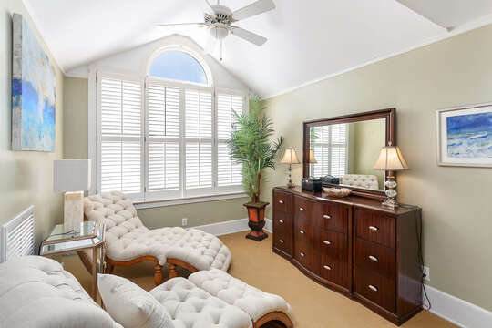 The lounge area of the master bedroom with lounge chairs and vanity dresser.