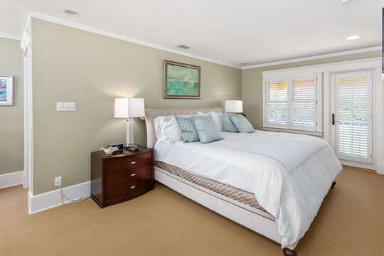 Bedroom with large bed and twin nightstands with lamps.