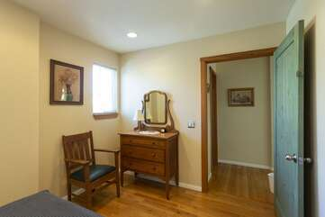 Upstairs bedroom has a dresser and closet.
