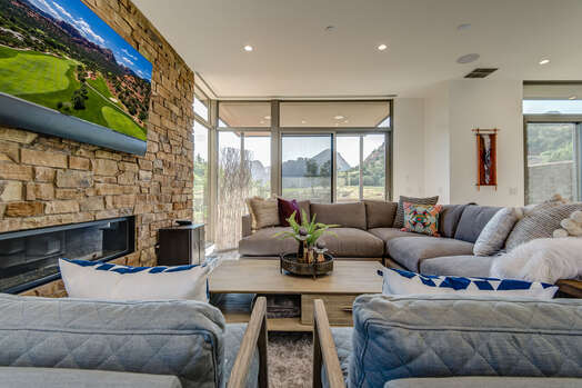 Large Sectional Sofa and Chairs Surrounding a Floor-to-Ceiling Stone Gas Fireplace and 65