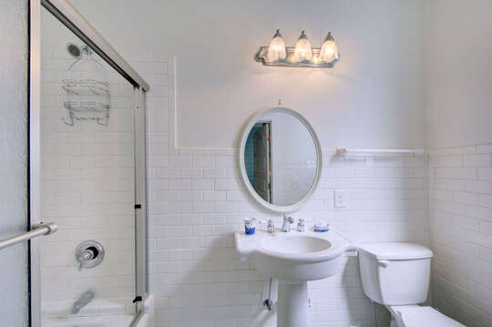 Tub and Shower Unit, Pedestal Sink, Mirror, Lamp, and Toilet.