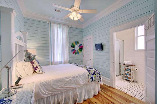 Large Bed, Ceiling Fan, Nightstand, TV, Mirror, and Bathroom Open Door.