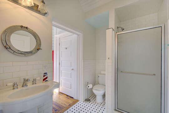 Pedestal Sink, Mirror, Toilet, and Shower.