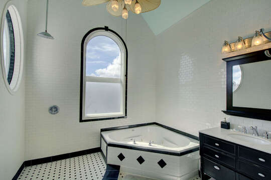 Hot Tub, Cabinet Vanity Sink, Mirror, Ceiling Fan, and Window.