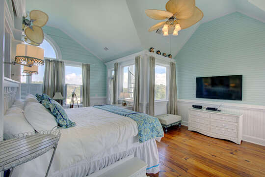 Bedroom with Multiple Windows, Drawer Dresser, TV, Ceiling Fan, and a Large Bed.
