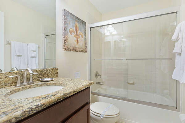 The ensuite bathroom features a dual vanity and shower/tub combination