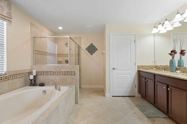 This master suite has an ensuite bathroom that features a dual vanity, walk in shower and garden tub