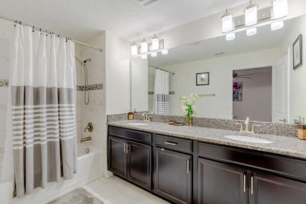 The ensuite bathroom includes a dual vanity and a bathtub and shower combination