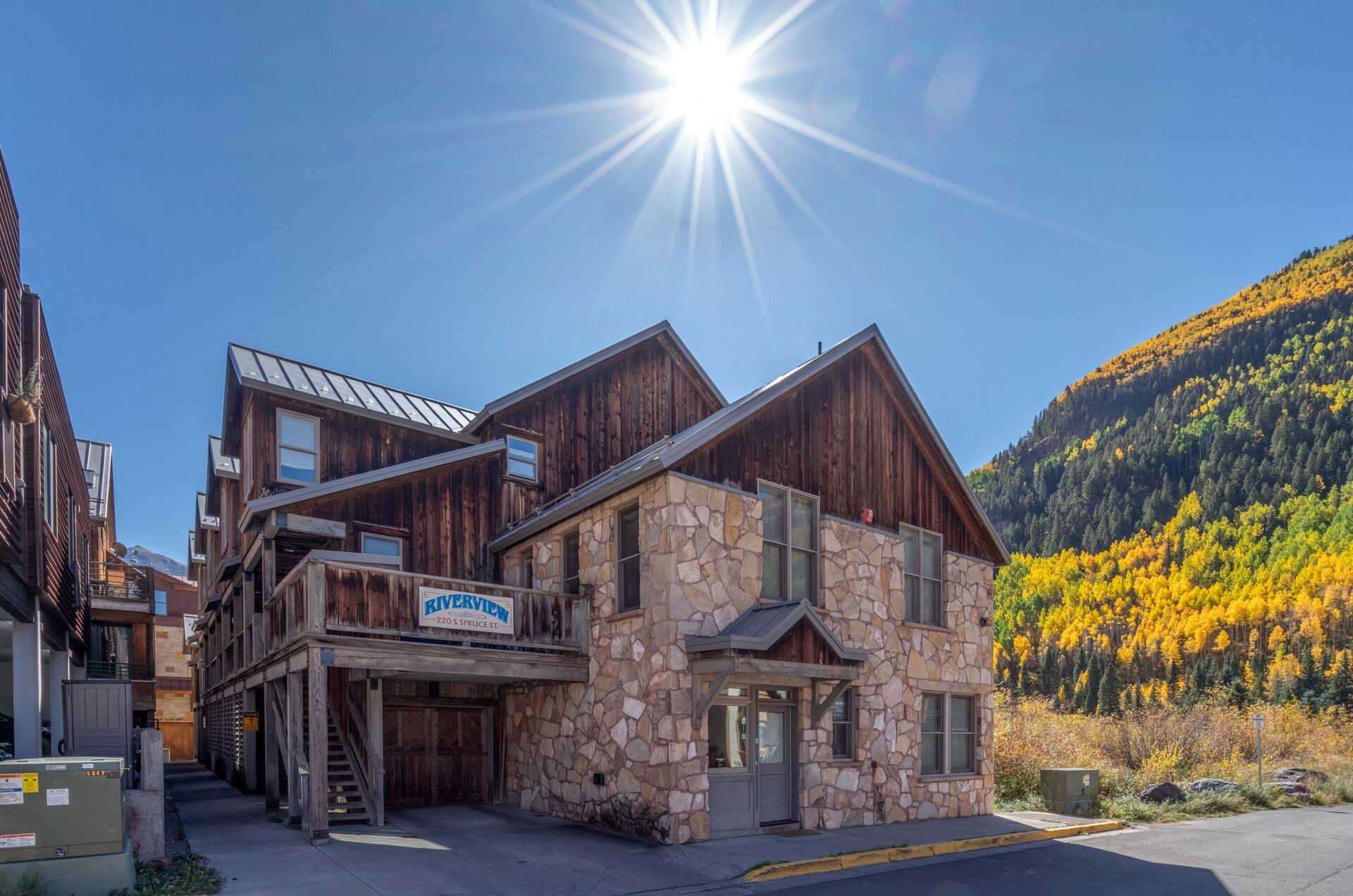 A view of the exterior of this 3 bedroom condo in Telluride, with the sun directly above it.