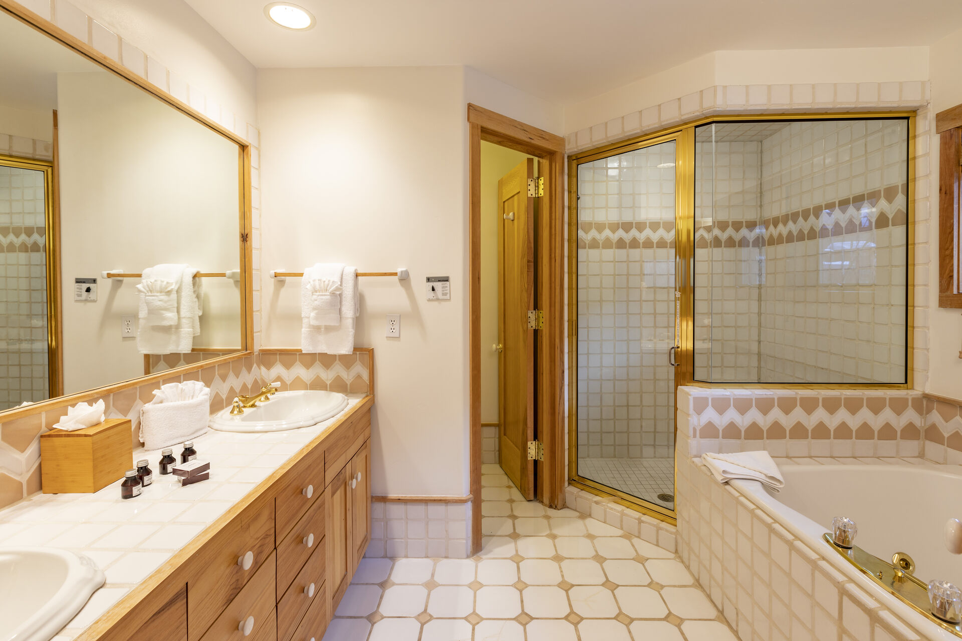 A bathroom in this 3 bedroom condo in Telluride with walk-in shower, separate toilet room, a spa tub, and double vanity sink.