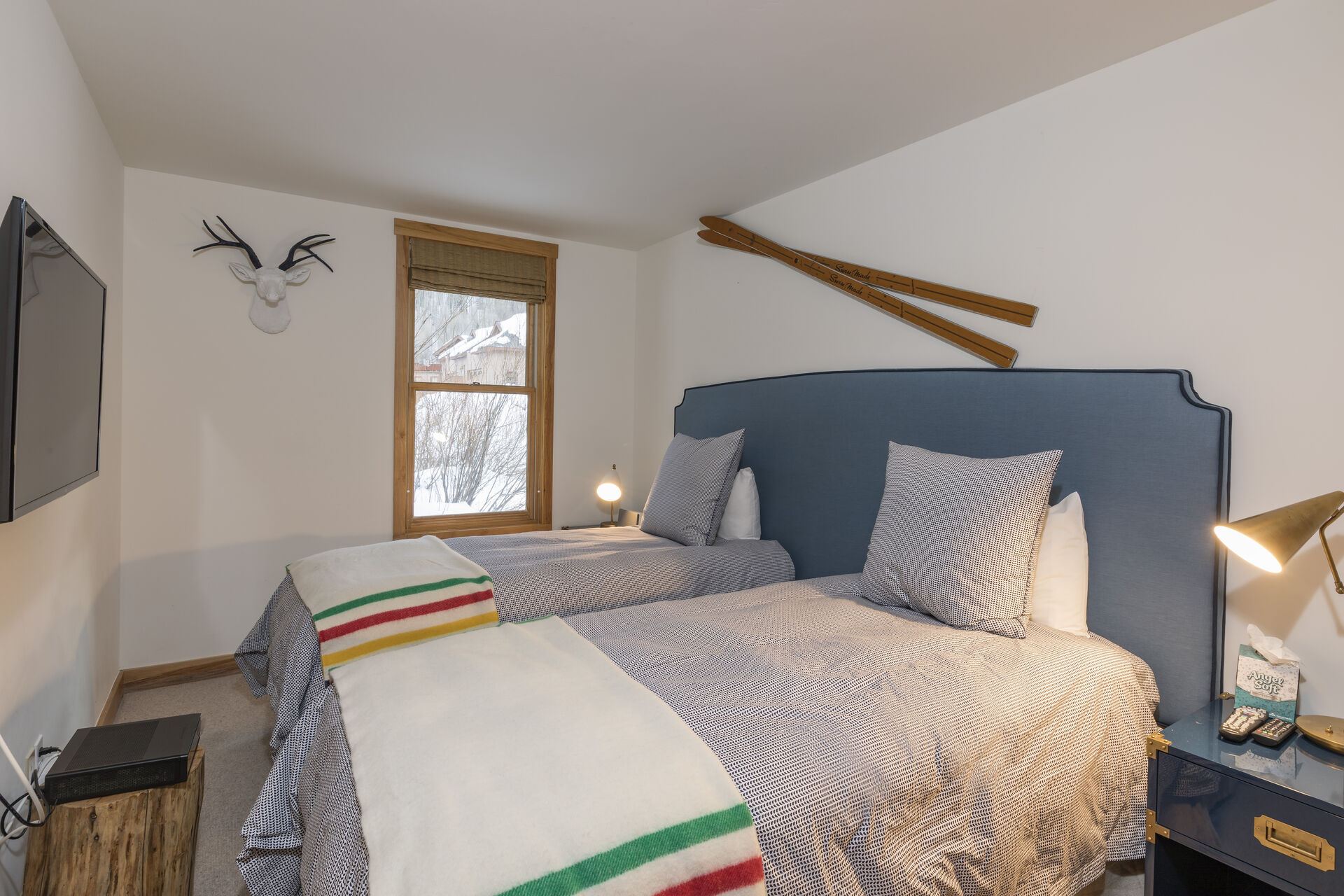 Two twin beds sharing a headboard in a bedroom across from a wall-mounted TV.