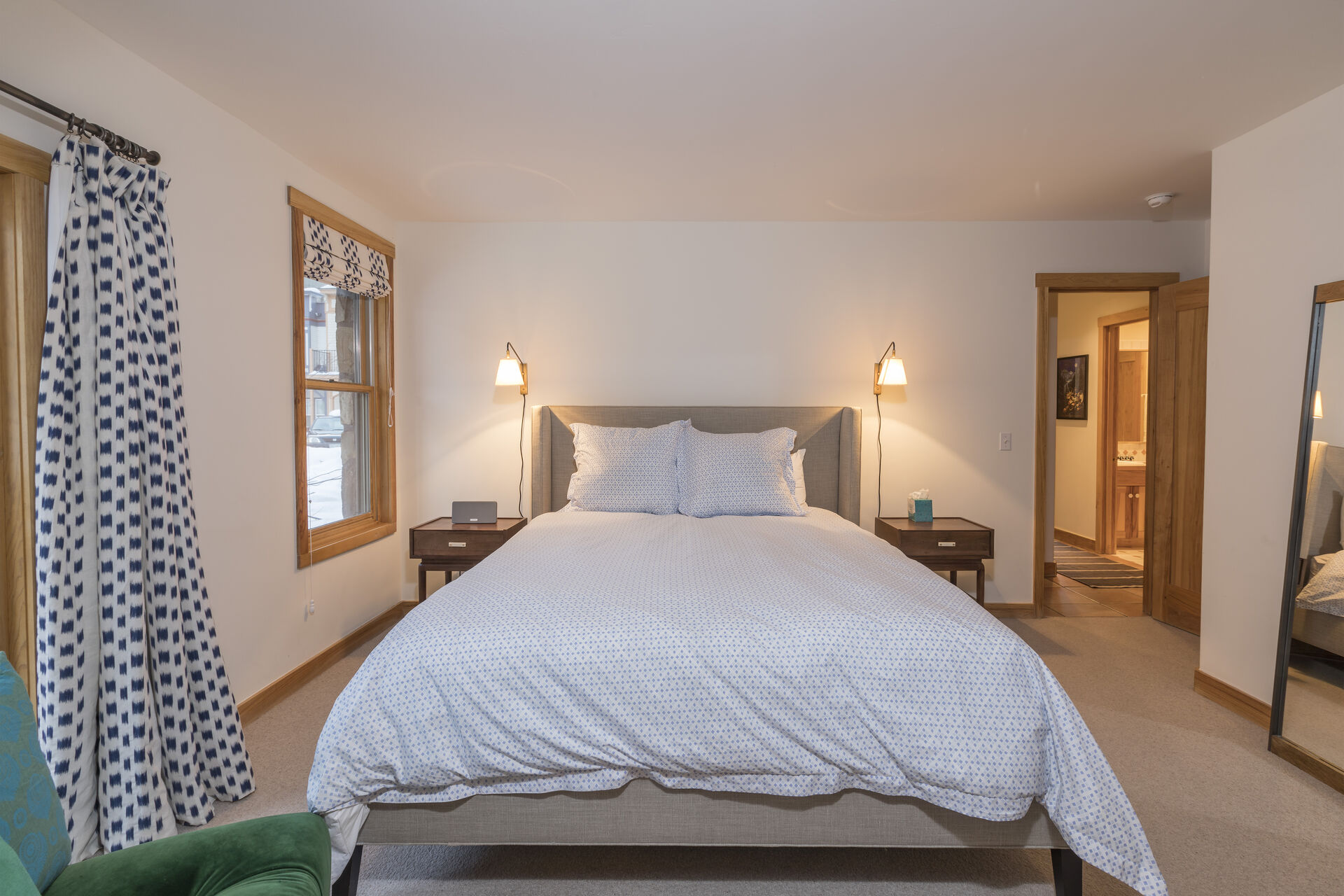 Large bed sits in the middle of a bedroom flanked on either side by nightstands.