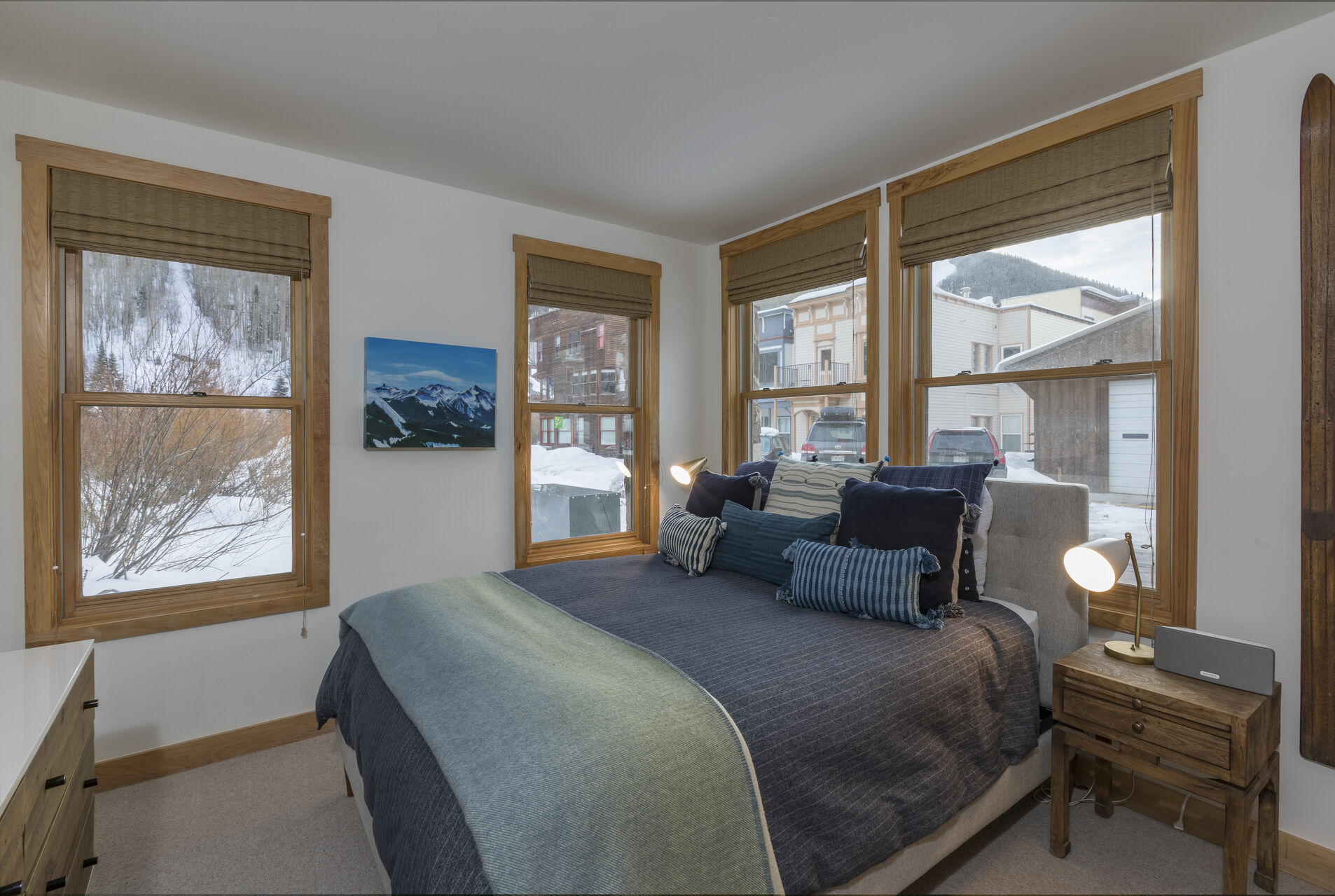 Large bed situated between many large windows, with a nightstand on the side.