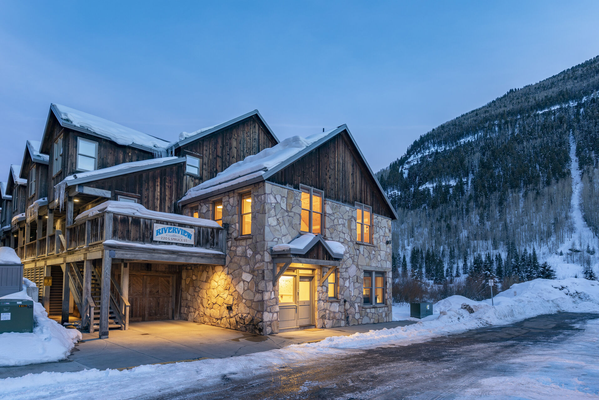Internal lights bring a glow to the snowy facade of this 3 bedroom condo in Telluride.