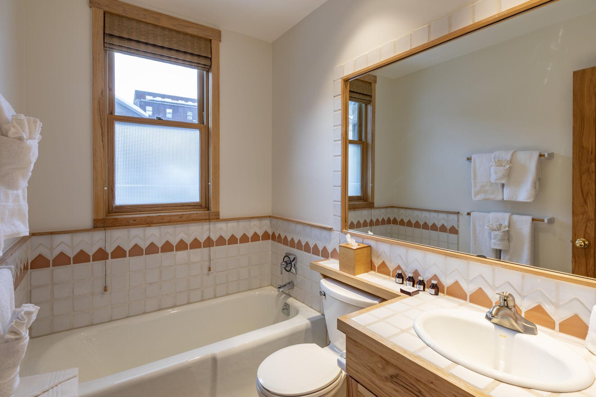 Bathroom with vanity sink, toilet, and tub.