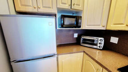 Kitchenette equipped with full-size fridge with freezer, microwave, toaster-oven, coffee-maker, dishes and utensils.