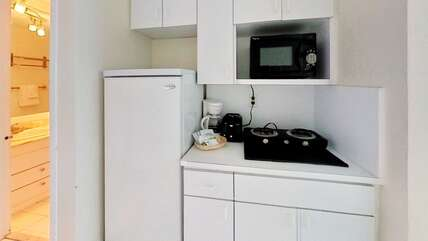 Kitchenette equipped with full-size fridge with freezer, double stove, microwave, coffee-maker, toaster, dishes and utensils.