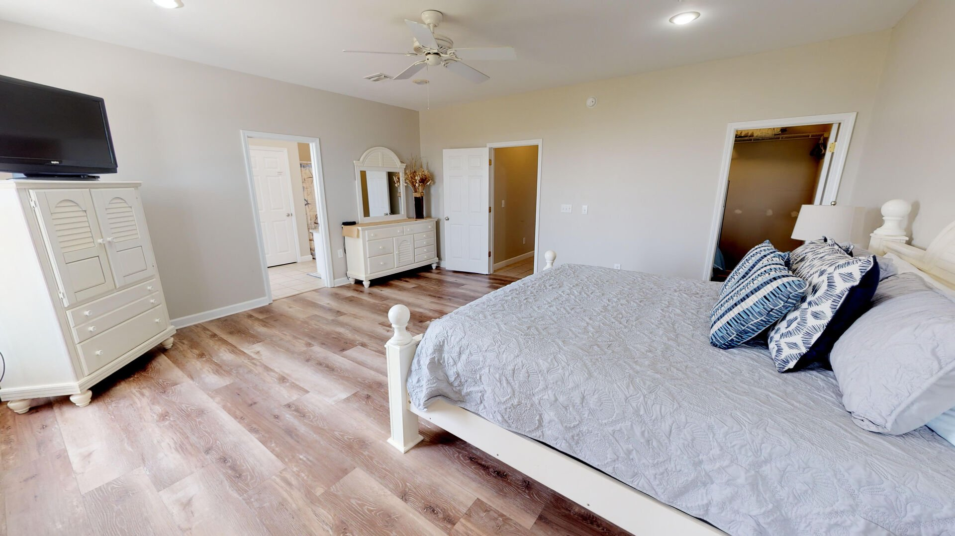 Spacious Bedroom Features Large Dresser and TV.