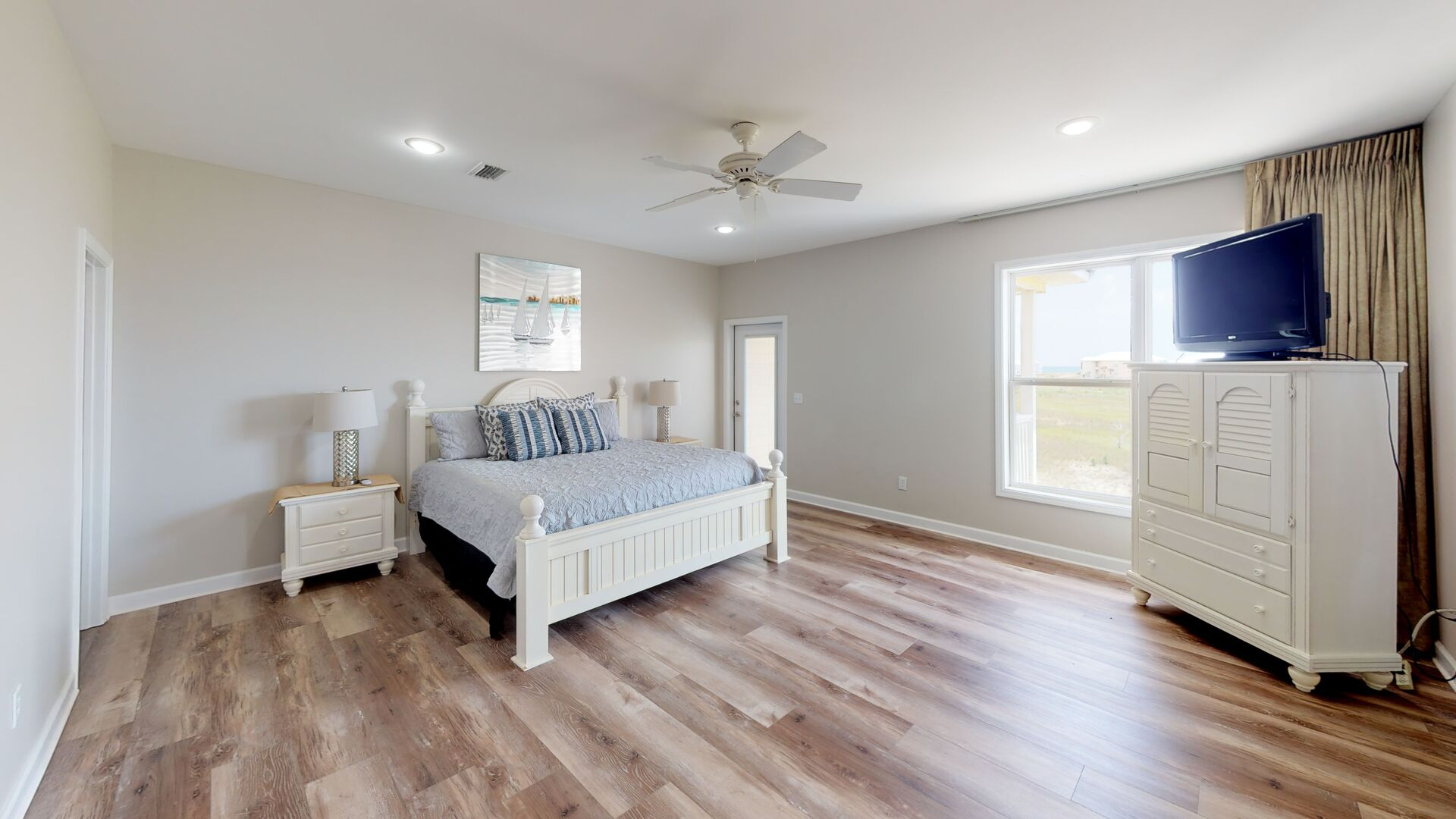 Large Bedroom Has Beautiful Floors and Large Windows.