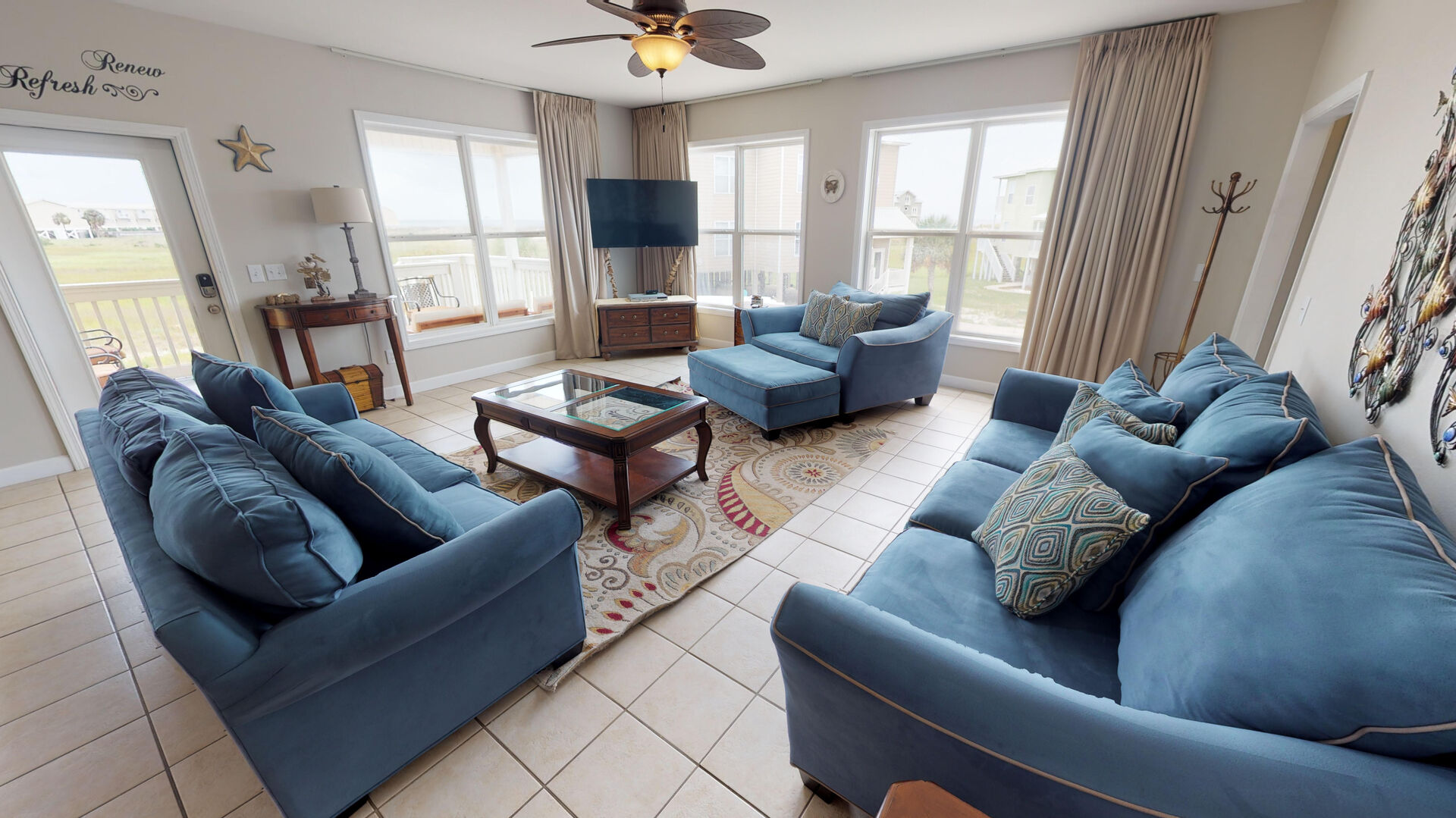 Living Area Features Two Blue Sofas and One Chair.