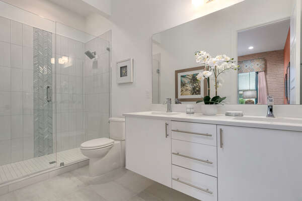 The modern ensuite bathroom with a walk-in shower and dual vanity sink