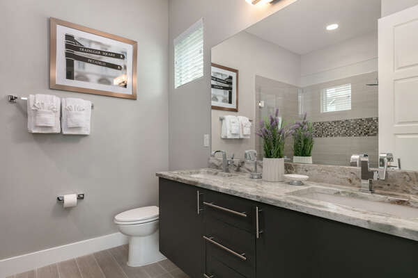 An Ensuite bathroom with dual vanity and walk in shower