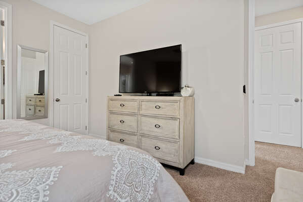 The room has a dresser for storage and TV