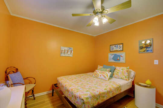 Large Bed, Nightstand, Ceiling Fan, and Chair.