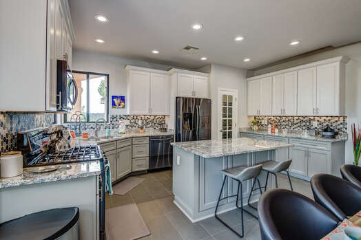 A Designer Chef's Kitchen with Dark Stainless Steel Appliances, Granite Countertops and Two-tone Shaker Cabinets