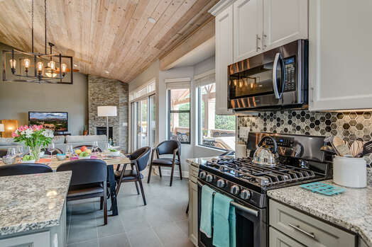 Fully Equipped Kitchen Including a 5-Burner Gas Stove with a Grill and Convection Oven, and Island Seating