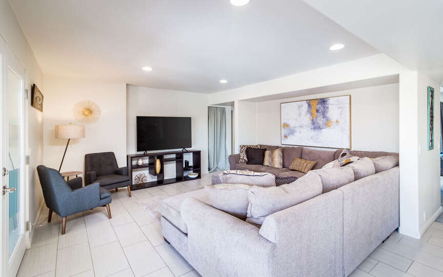 Living Area with Modular Sofa, Two Armchairs, and TV.