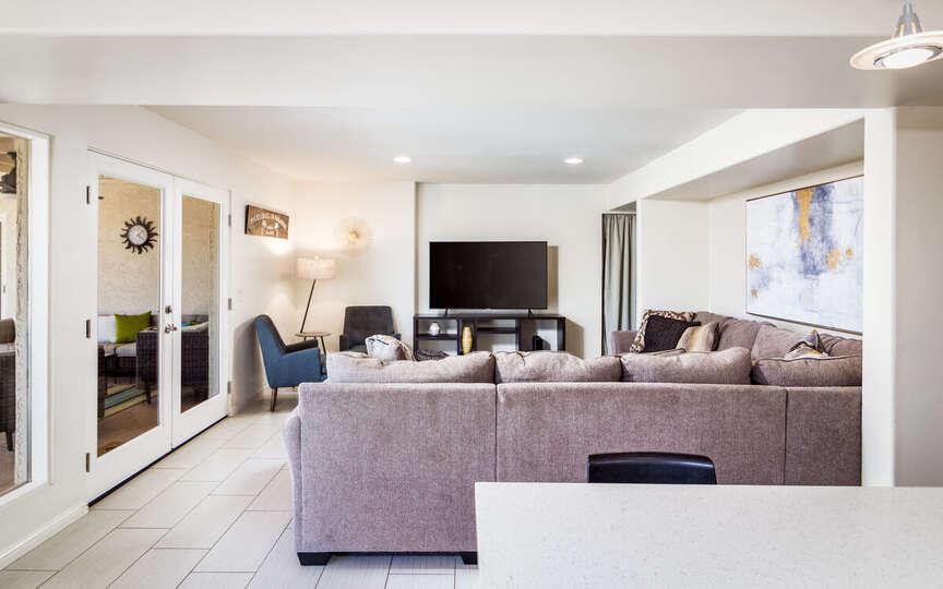Modular Sofa, Armchairs, Patio Doors, and TV.