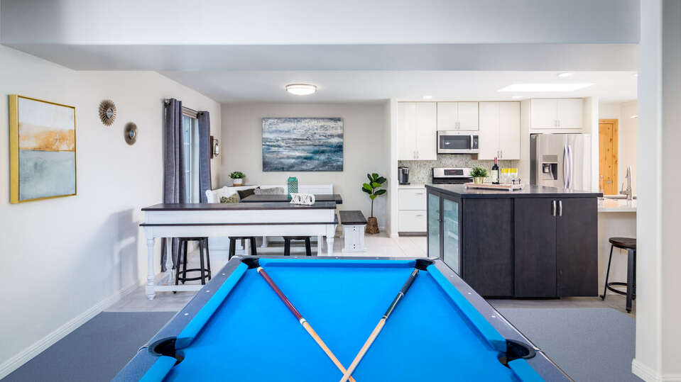 Pool Table, High Table, Stools, Kitchen with Island, Refrigerator, and Microwave.