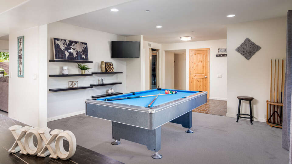 Game Room with Pool Table, Floor Cue Rack, and TV.