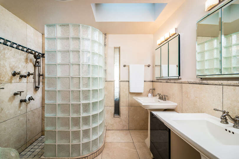 Bathroom with Walk-In Glass Block Shower, Two Pedestal Sinks, and Mirrors.