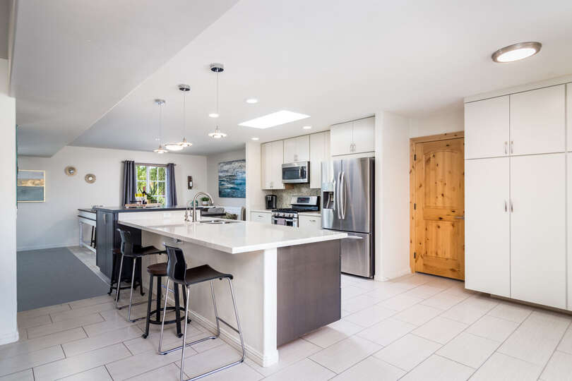 Kitchen with Island, Bar Stools, Refrigerator, Microwave, and Pantry Doors.