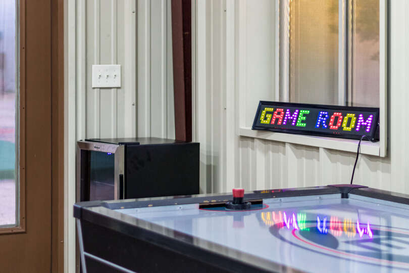 Game Room Sign, Air Hockey Table, and a Mini Fridge with Glass Door.