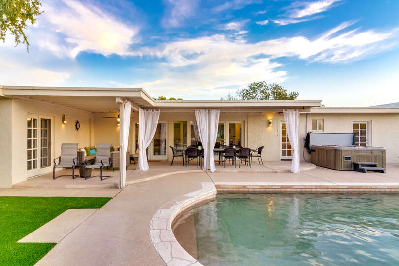 Backyard Porch with Patio Tables and Chairs, Pool and Jacuzzi.