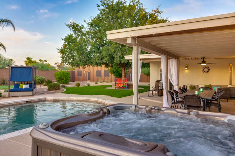 The Jacuzzi and Pool on the Backyard with a View of Seating Area.