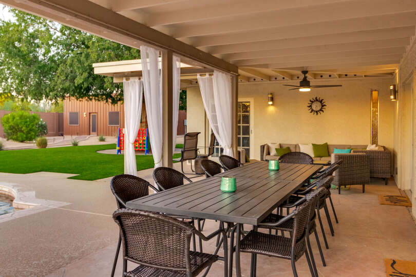 Backyard Seating Area with Patio Table, Chairs, Sofa, and Ceiling Fan.
