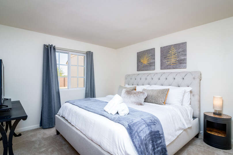 Bedroom with Large Bed, Nightstand, Lamp, and TV.