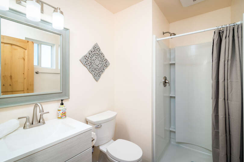 Bathroom with Shower, Toilet, Sink, and Mirror.