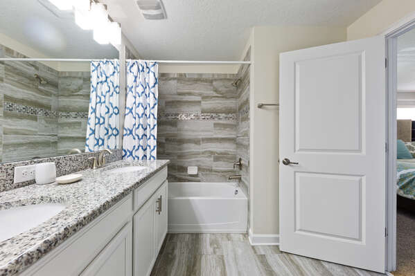 This large ensuite bathroom has a shower/tub combination and a dual vanity