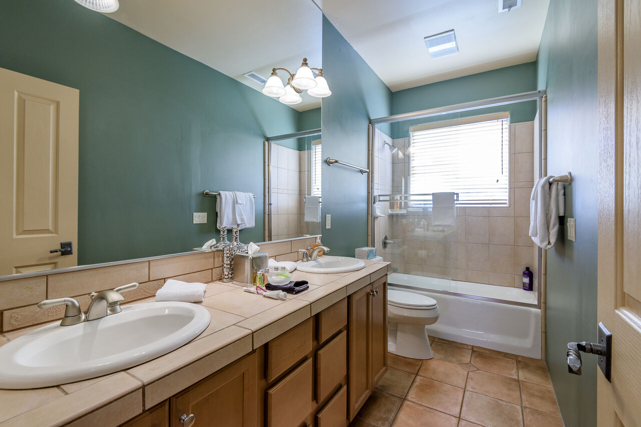 Full Shared Bathroom with Dual Sinks and a Tub/Shower Combo