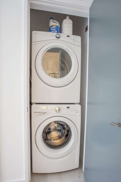 The laundry Area Features a Stacked Washer and Dryer.
