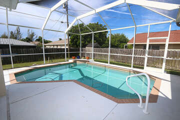 Pool with screened in lanai and privacy fenced in back yard