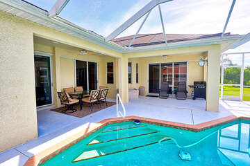 Pool with screened in lanai with dining and grill