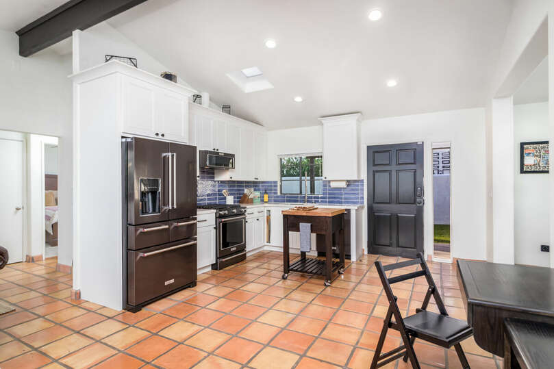 Large full kitchen, with gas stove, cutting board island, stainless steel sink, and, more.