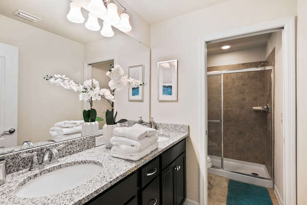 The shared bathroom has a dual vanity and a walk-in shower